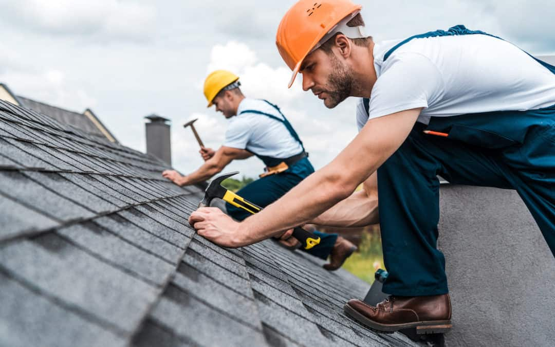 two men with hard hats repairing a roof on a cloudy day